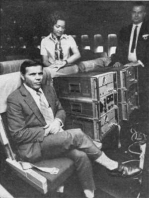 Οι Hafele και Keating πάνω σε ένα εμπορικό αεροσκάφος, με δύο από τα ατομικά ρολόγια τους και μια αεροσυνοδός.